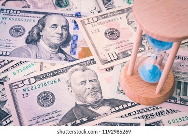 Hourglass or sandglass on US dollar banknote. Concept world economic of time to consider raise interest rate via FED (Federal Reserve System), the central banking system of United States of America.