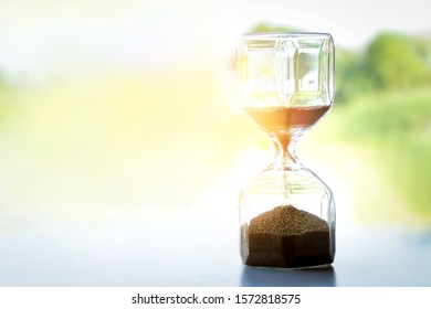 The hourglass is set on a white surface, consisting of 2 glass tubes that are connected by a narrow channel. And has sand packed inside. with copy space.