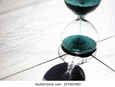 hourglass with shadow on grey wooden background. Sand running through the bulbs of an hourglass measuring the passing time in a countdown to a deadline, on a bright background with copy-space