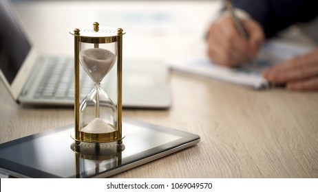 Hourglass standing on table with sand trickling, man working with graphs, data, stock footage