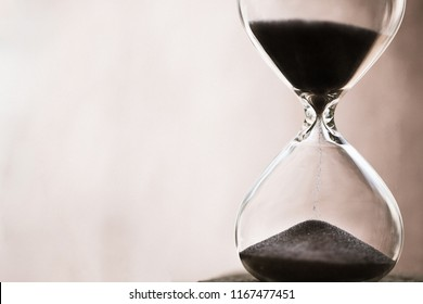 Hourglass as time passing concept for business deadline, urgency and running out of time. Sandglass, egg timer with brown backgrou showing the last second or last minute or time out.  With copy space.