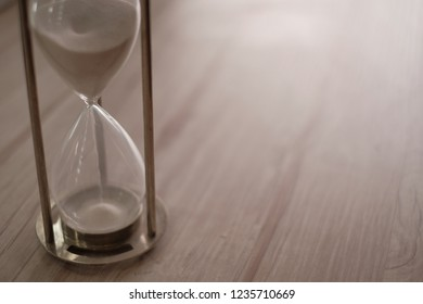 Hourglass as time passing concept for business deadline, Sand running through the bulbs , urgency and running out of time, wooden background with copy space.