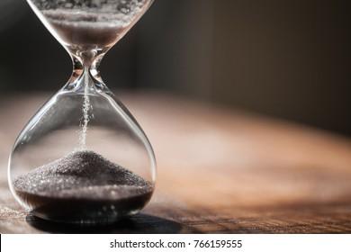 Ampulheta como conceito de passagem de tempo para o prazo de negócios, urgência e esgotamento do tempo. Sandglass, temporizador de ovo no chão de madeira mostrando o último segundo ou último minuto ou tempo limite. Com espaço de cópia.