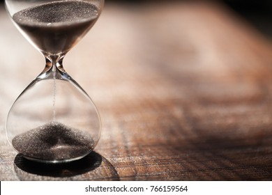 Hourglass as time passing concept for business deadline, urgency and running out of time. Sandglass, egg timer on wooden floor showing the last second or last minute or time out.  With copy space.