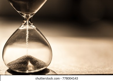 Hourglass as time passing concept for business deadline, urgency and running out of time. Sandglass, egg timer on wooden floor showing the last second, last minute or time out.  With copy space. Aged.