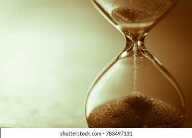 Hourglass as time passing concept for business deadline, urgency and running out of time. Sandglass, egg timer on wooden floor showing the last second, last minute or time out.  Aged tone, copy space.