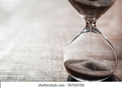 Hourglass as time passing concept for business deadline, urgency and running out of time. With wooden background and copy space. Sandglass.