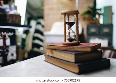 Hourglass in vintage style with old books, Antique Sand Clock, Read education concept