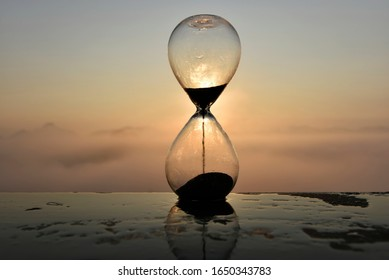 A hourglass (with falling sand) on a wooden wet table with sea of fog and mountain range silhouette in sunrise time