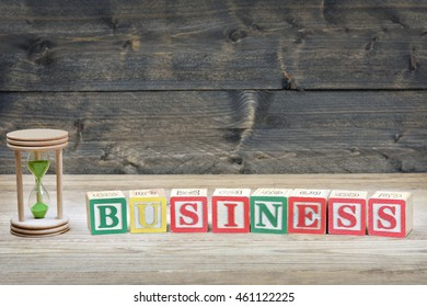 Hourglass and word business on wooden table