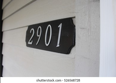 House address on gray wooden siding