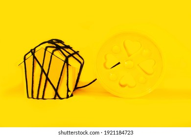 House arrest during lockdown is depicted through black cable strings of a yellow disc toy. The home, the toy, and the backdrop are all in the color of yellow. Stay at home. Stay Safe.