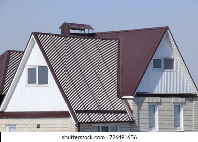 The house is with an attic and a combined roof. Roofing of metal profile wavy shape on the house with plastic windows. House with plastic windows and a brown roof of corrugated sheet.