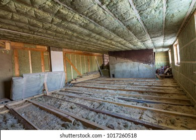 House attic under construction. Mansard walls and ceiling insulation with rock wool. Fiberglass insulation material in wooden frame for cold barrier.