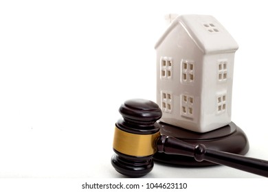 House Auction, property foreclosure and buying a new home concept with a white house model and a gavel isolated on white background with copy space