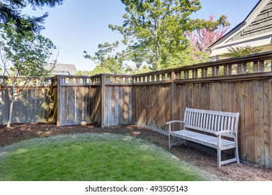 House back yard with wooden bench standing alone by the fence. Northwest, USA