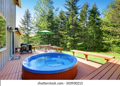 House backyard with hot tub, barbecue and patio table set. Northwest, USa