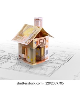 House from banknotes on building plan, top isolated