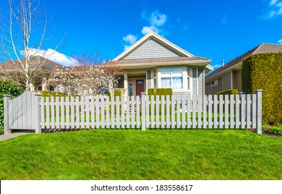 House behind country style long wooden fence with nicely trimmed grass.