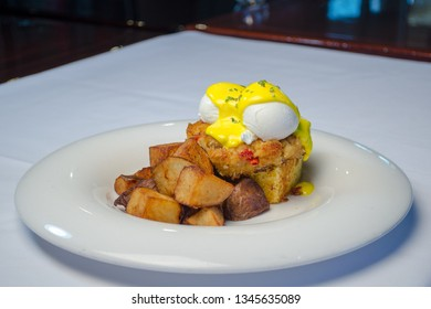 HOUSE BENEDICT  Two poached eggs served over a crab cake and cornbread then topped with hollandaise sauce and a crispy potato pancake.