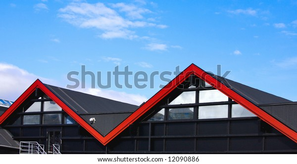 The  house with a black roof and a red strip on it on a background of the of the blue sky