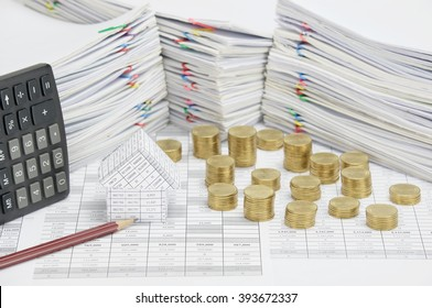 House and brown pencil on finance account have pile of gold coins and calculator place vertical with overload of paperwork with colorful paperclip as background. Business and finance concept success.