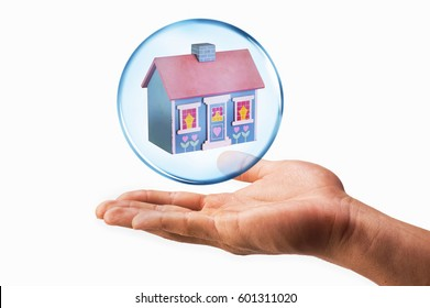 House in a bubble with hand under it.