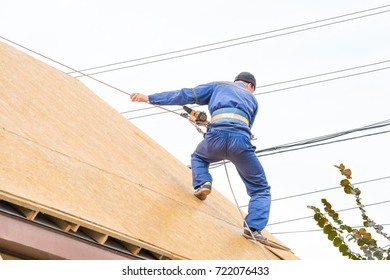 House builder repairs the roof balancing with wire on the rooftop