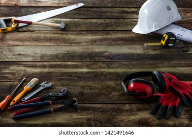 house building, carpentry, renovation tools and safety equipment for engineer, architect, construction workman over rustic wooden background, copy space