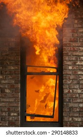 A house burns with flames shooting out the window.
