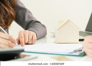House buyer signs paper regarding house buying with real estate agent. Selective focus at wooden house model. Concept of decisions and laws of buying a house.