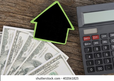 House with Calculator and Dollars On Wood Background, Costing and Budget Concept