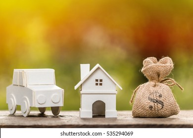 A house and car model and money bag for loans concept.