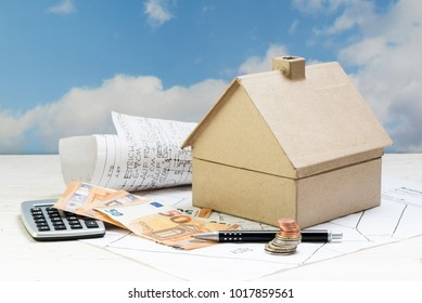 house from cardboard with money and calculator standing on architecture plans against a blue sky with clouds, copy space, selected focus