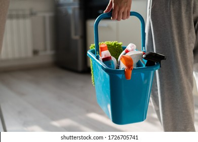 House cleaning concept. Faceless woman holds cleaning products in a blue basket. Closeup of the hands of a female workers house.