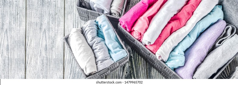 House cleaning concept. Vertical tidying up storage. Marie Kondo tidying method. Neatly folded clothes in the organizer boxes for wardrobe. Wooden background copy space above banner