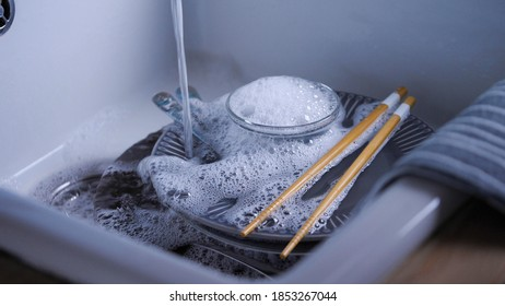 House Cleaning routine. Water streaming on dishes in kitchen sink. Hand washing dishes. Blue dishes and Chinese chopsticks. Home water energy saving.