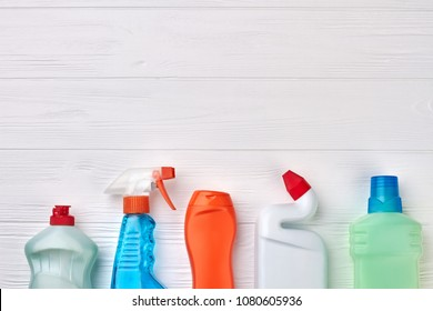 House cleaning supplies on wooden background. Row of plastic bottles with cleaning liquid on wood, copy space on top.