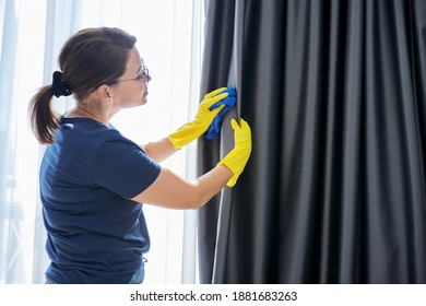 House cleaning, woman in gloves with a rag cleaning curtains. Housework, housekeeping, household, cleanliness concept