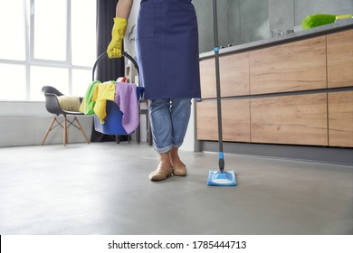 House cleaning. Woman holding mop and plastic bucket or basket with rags, detergents and different cleaning products while standing in the kitchen at home. Housework, cleaning, housekeeping concept