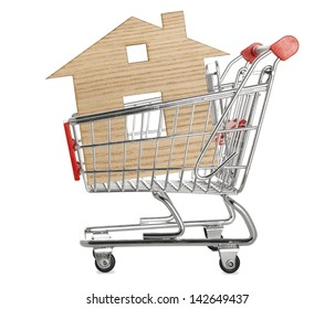 House concept - model of the house in shopping cart on white background