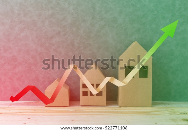 house concept with house shape cardboard on wooden floor and grey wall with free copyspace for your creativity ideas text
