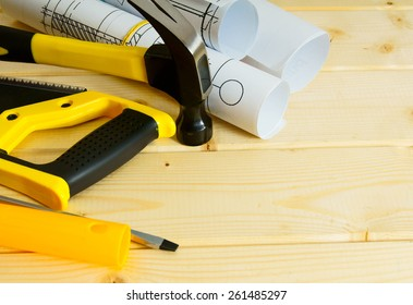 House construction. Repair work. Drawings for building,saw, hammer and others tools on wooden background.