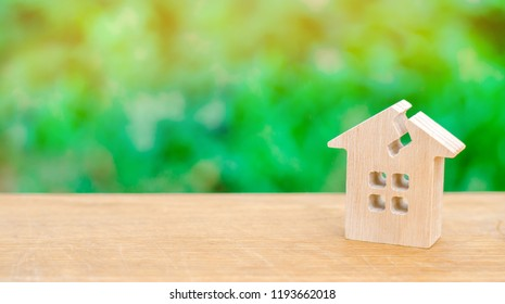 House with a crack. Damaged house due to old age or natural disaster. Repair and renovation of the building and property. Shabby housing. Replacing the old housing with a new one.
