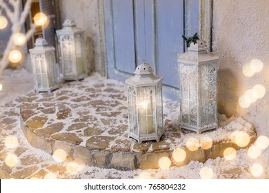 House decorated for Christmas. Luminous lanterns on snowy stairs at porch. Beautiful winter christmas background.
