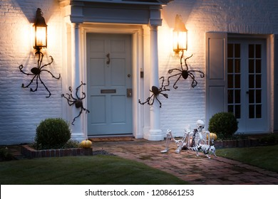 The house is decorated for Halloween: Huge black spiders crawl around the house, and on the path there is a resting human skeleton with the dog's skeleton.. Night, Houston, Texas, United States