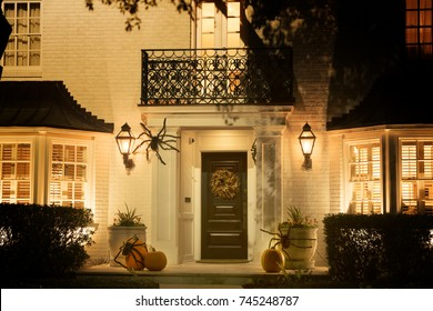 The house is decorated for Halloween: pumpkins with spiders, a wreath on the door. Night