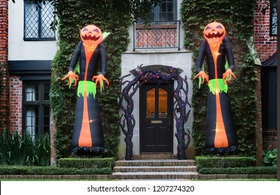 The house is decorated for Halloween: Two huge inflatable monsters with pumpkin heads stand at the entrance to the house. Night, Houston, Texas, United States