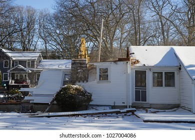 house demolition by an excavator in the winter
