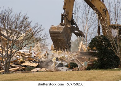 House demolition with an industrial excavator leveling the destroyed residence.